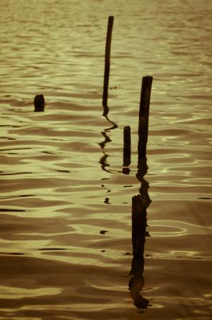 definite: Pier poke sticks in water Stock Photo