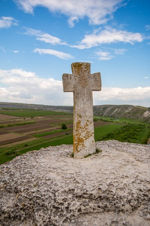 Old stone cross. Ancient christian place Orhei, Moldova Republic. Summer hills and fields view . Stock Photo