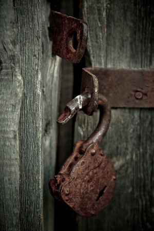 Old rusty opened lock without key. Vintage wooden door, close up concept photo.