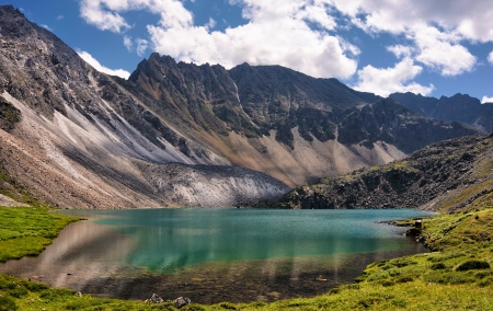 Mountain Lake in the alpine tundra of mountain peaks. Emerald color of pure water comes from a very large depth Stock Photo - 14786874