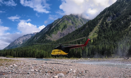 flight mode: Flying a helicopter in horizontal flight mode at low altitude over the valley of a mountain river. Eastern Sayan. Siberia