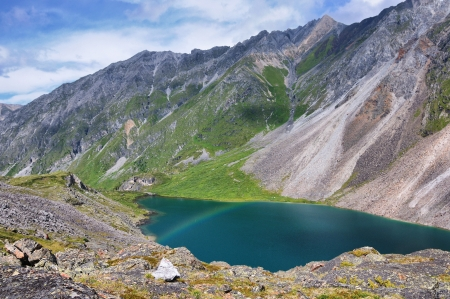 A small rainbow over the lake in the mountains. Subalpine zone in the Eastern Sayan Mountains photo