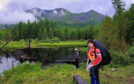 Female tourists against a small lake in the foothills of the Eastern Sayan. hiking Stock Photo - 14909275