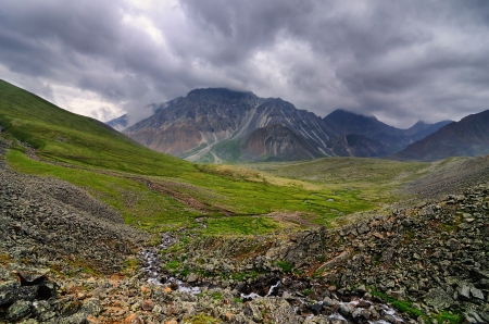 Cloudy sky over the alpine tundra at the origins of the mountain river Stock Photo