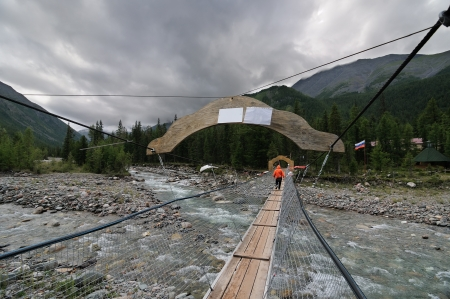 A pedestrian suspension bridge across mountain river photo