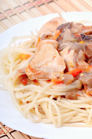 Italian spaghetti with goulash of chicken breasts, mushrooms and carrots Stock Photo