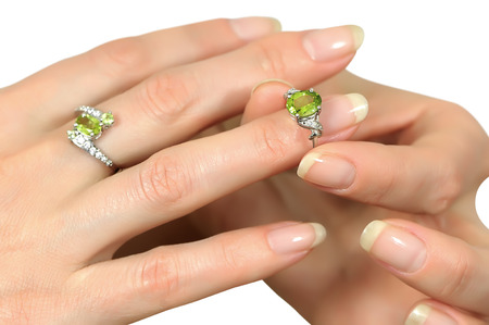 Donning a silver ring with a precious stone peridot ring finger on a beautiful female hand