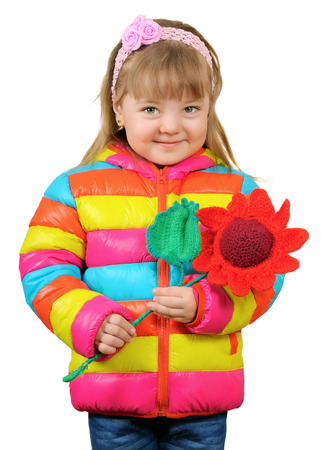 Smiling three year old girl in bright clothes holding a knitted crochet flower