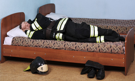 Firefighter sleeping dressed in Bunker gear on the bed Stock Photo