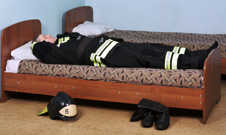 turnout gear: Sleeping fireman lying on the bed in the room Stock Photo