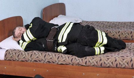Dressed sleeping fireman lying on the bed in the room