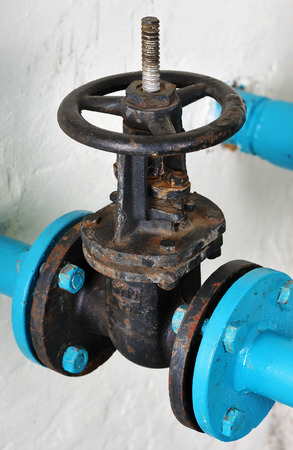 cast off: Unpainted water valve made of cast iron on the background of whitewashed walls