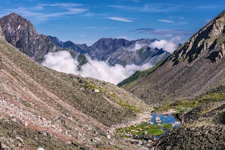 tunka range: Mountain slopes with stone talus and a small lake at the bottom. Eastern Sayan. Buryatia