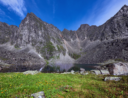tunka range: Small meadow near a mountain lake on the background of a mountain range on a sunny summer day. Eastern Sayan. Buryatia Stock Photo