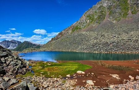 eastern sayan: Patch of green grass on the edge of a mountain lake in a hanging valley between the rock fragments. Eastern Sayan. Buryatia Stock Photo