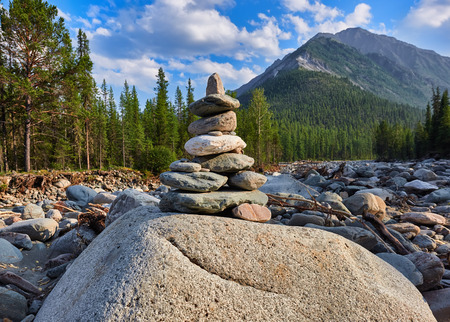 tunka range: Cairn. Pyramid of stones. Siberian mountain river valley Shumak. Eastern Sayan. Russia. Shallow depth of field, focus on the Pyramid
