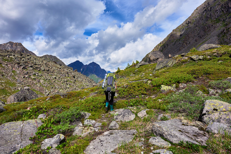Hiking. Mountain tourism . A woman with a large backpack in rubber boots walks on a mountain path
