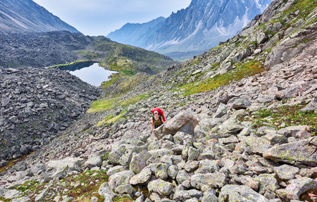 Hiking. Woman climbs the slope between large stones . Eastern Siberia. Russia