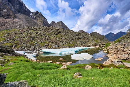 tunka range: Alpine meadow with green onions at a small lake with ice. Eastern Sayan . Russia