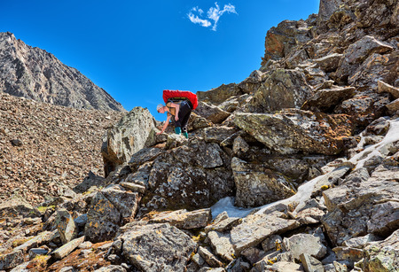 descends: Hiking. Woman with a backpack gently descends on large boulders . Mountains of Eastern Siberia