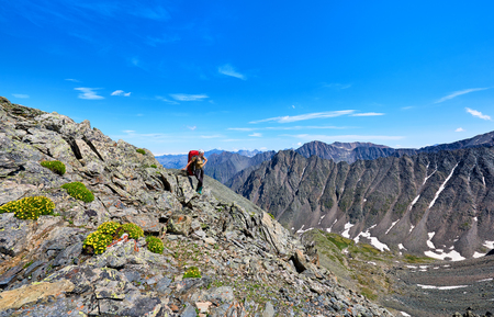tunka range: Pass hopping. Woman with a backpack on background of mountain peaks high in mountains . Eastern Sayan . Russia