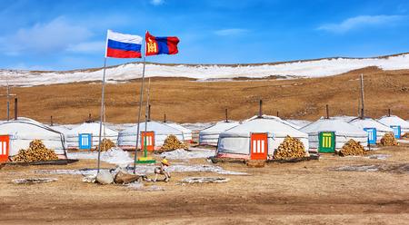 Russian and Mongolian flag next to yurts . Mongolia