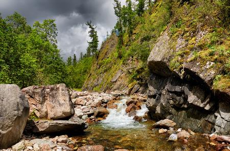Mountain stream in small rock. Eastern Sayan . Russia