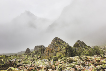 tunka range: Fog in mountains and boulders covered with lichen in foreground . Eastern Sayan . Russia Stock Photo