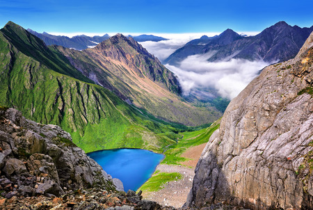 Low clouds in valley of lake. View from mountain foot of pass. Eastern Sayan. Russia Stock Photo