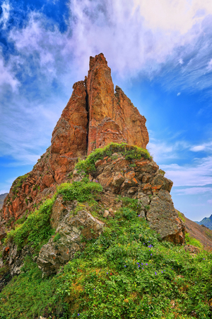 Pointed steep red rock on watershed ridge. Below is a typical vegetation of alpine meadows in South Siberia. Eastern Sayan. Russia