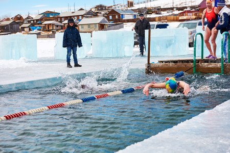 SAHYURTA ,IRKUTSK REGION, RUSSIA - March 11.2017: Cup of Baikal. Winter Swimming. Butterfly. Two women compete for speed