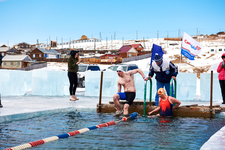 SAHYURTA ,IRKUTSK REGION, RUSSIA - March 11.2017: Cup of Baikal. Winter Swimming. Butterfly. Man and woman are preparing for swim