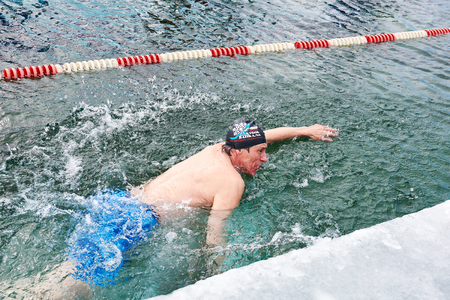 very cold: SAHYURTA, IRKUTSK REGION, RUSSIA - March 11.2017: Cup of Baikal. Winter Swimming Competitions. One man swims with a freestyle in very cold water