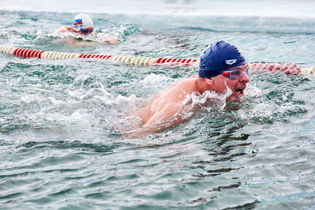 SAHYURTA, IRKUTSK REGION, RUSSIA - March 11.2017: Cup of Baikal. Winter Swimming Competitions. Swimmer breathes deep air before immersing face in water