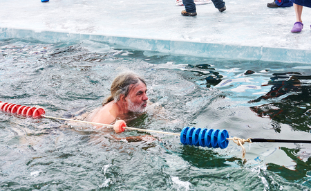 SAHYURTA, IRKUTSK REGION, RUSSIA - March 11.2017: Cup of Baikal. Winter Swimming Competitions. Breaststroke. An elderly man with gray beard and without cap floats in very cold water