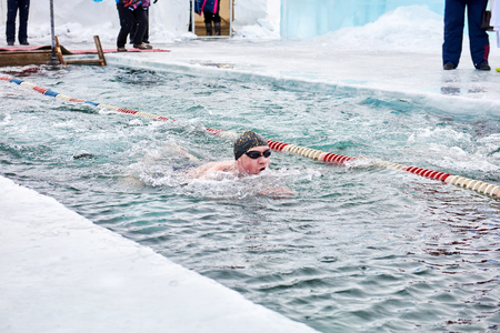 SAHYURTA, IRKUTSK REGION, RUSSIA - March 11.2017: Cup of Baikal. Winter Swimming Competitions. One swimmer moves very fast in very cold water in a hole
