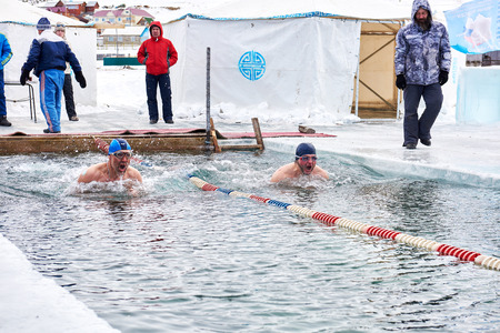 SAHYURTA, IRKUTSK REGION, RUSSIA - March 11.2017: Cup of Baikal. Winter Swimming Competitions. Two swimmers make quick breath before diving