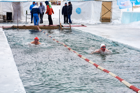 SAHYURTA, IRKUTSK REGION, RUSSIA - March 11.2017: Cup of Baikal. Winter Swimming Competitions. Two swimmers compete for speed breaststroke. Chinese and Russian athletes. Chinese man in red cap Editorial