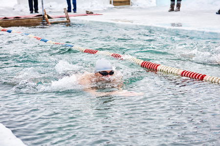 SAHYURTA, IRKUTSK REGION, RUSSIA - March 11.2017: Cup of Baikal. Winter Swimming Competitions. One man is swimming on water path with breaststroke