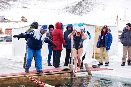 SAHYURTA, IRKUTSK REGION, RUSSIA - March 11.2017: Cup of Baikal. Winter Swimming Competitions. Referee talks to woman before start on edge of hole