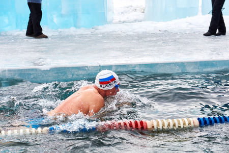 SAHYURTA, IRKUTSK REGION, RUSSIA - March 11.2017: Cup of Baikal. Winter Swimming Competitions.A swimmer in white hat with an inscription Russia and flag