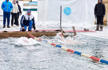 SAHYURTA, IRKUTSK REGION, RUSSIA - March 11.2017: Cup of Baikal. Winter Swimming Competitions. Start swimmers. Referee - Alexander Zelenetsky, three-time world champion in winter swimming Editorial