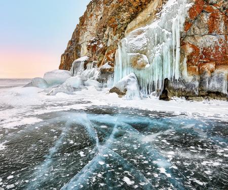 Cracks on clear ice near Baikal cape and icicles of splash ice on coastal rock. Lake Baikal. Olkhon Island