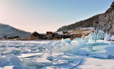 Ice hummocks on Lake Baikal near a small village. Evening in early March. Olkhon Island. Irkutsk region. Russia
