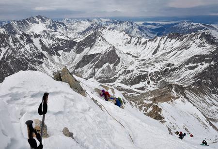 MUNKU-SARDYK, BURYATIA, RUSSIA-April 29,2017: Climbing peak of Munku-Sardyk in background of mountain massif. Mountaineers move around with their hands on rope