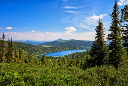 Lake Bright in dark coniferous taiga. Nature Park Ergaki. Krasnoyarsk region. Russia