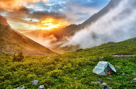 Dawn in Siberian mountains. Tourist tent on slope of tundra. East Sayan. Buryatia. Russia