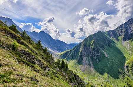 Mountain valley. View of descent from pass. Steep slope of tundra with rare small Siberian pines. Russia Stock Photo
