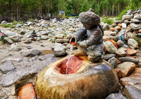 ARSHAN, BURYATIA, RUSSIA - July 17, 2017: Sculpture Boy with a pitcher aon mineral spring Hubuun. Healing water flows directly from pitcher of sculpture into stone niche. Popular source for suffering