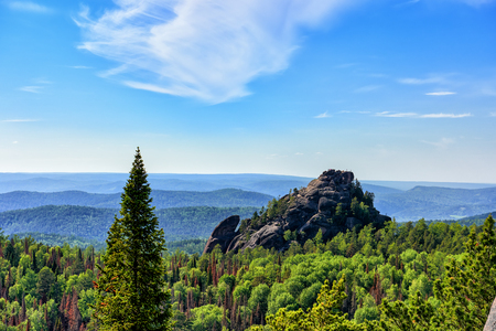 Stolby Nature Sanctuary (The Pillars). View from fourth pillar to rock complex The First Pillar. People stand on a rock and admire surrounding views. Krasnoyarsk region. Russia